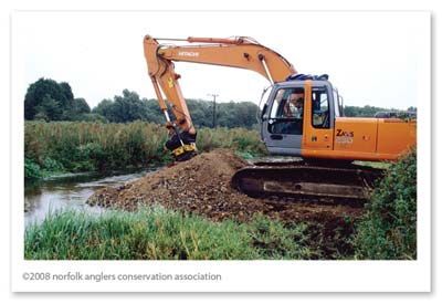 Digger depositing aggregate into riffle